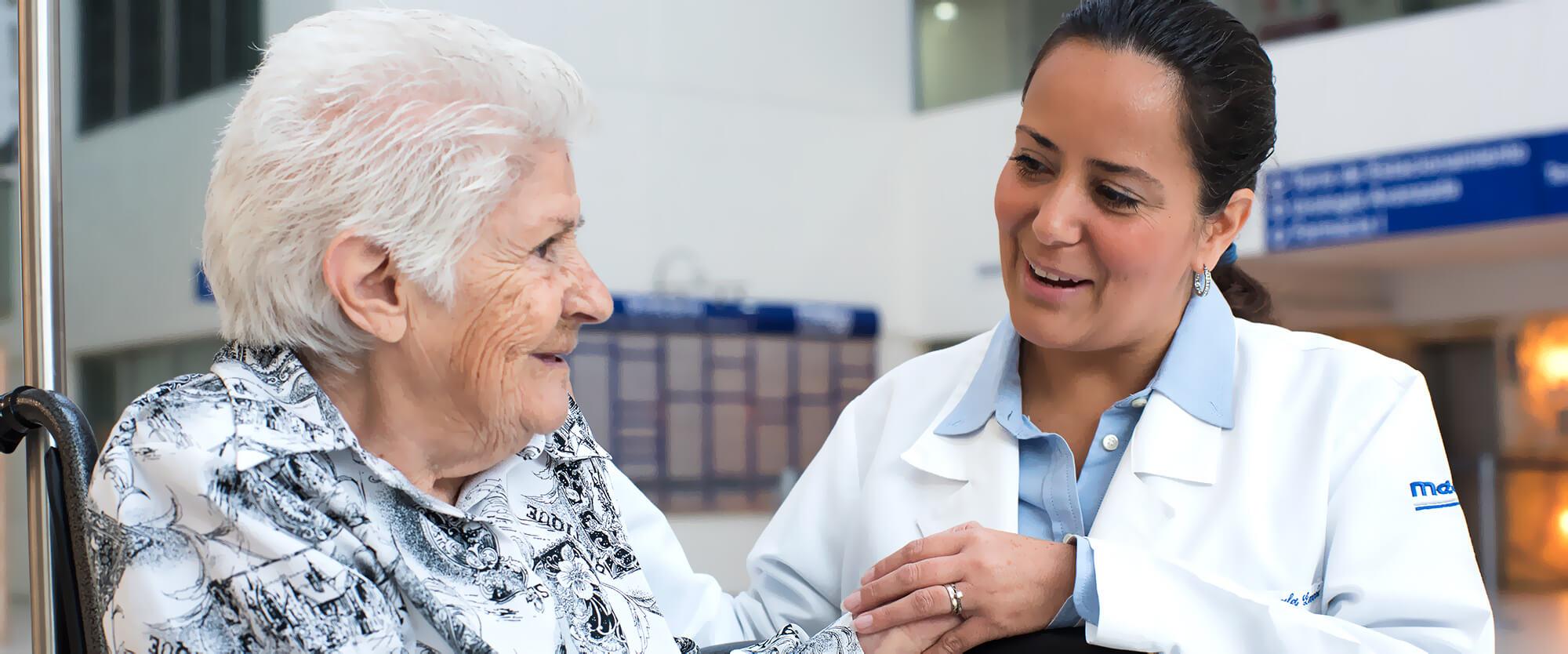 Doctora acompañando a paciente extranjera en silla de ruedas.
